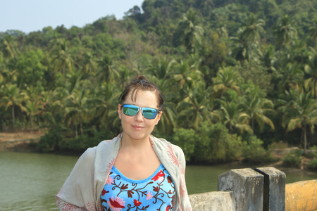 Beautuful girl posing on the brige near tropical forest photo
