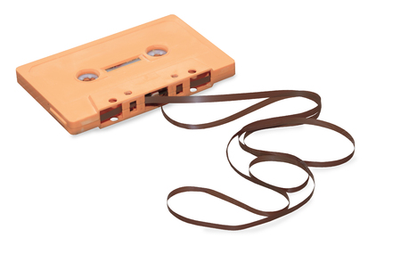 Vintage orange audio cassette with magnetic tape isolated over white background Stock Photo