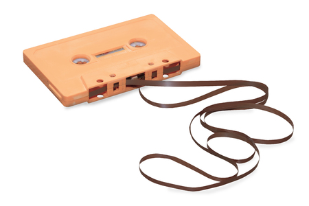 vintage orange audio cassette with magnetic tape isolated over white