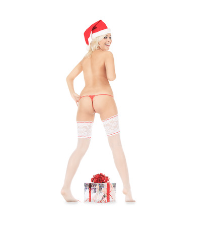 Wonderful female in santa hat and white stockings with christmas gift