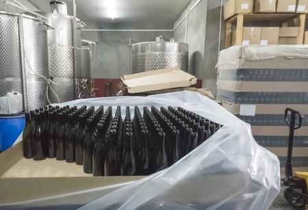 Feeding bottles to the conveyor for further bottling of wine 版權商用圖片