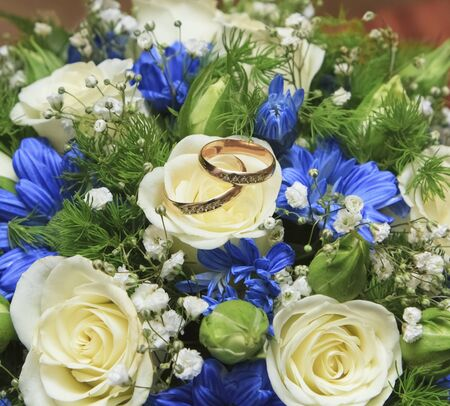 Golden wedding rings with bouquet. Focus on the rings Stock Photo