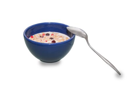 Spoon and Bowl of oatmeal porridge with banana, blueberries, almonds, coconut and caramel