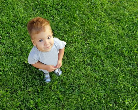 Boy looking up with a smile, standing on green grass