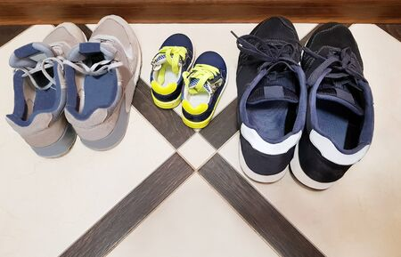 Dad, mom, son - a happy family. Three pairs of sneakers on the floor