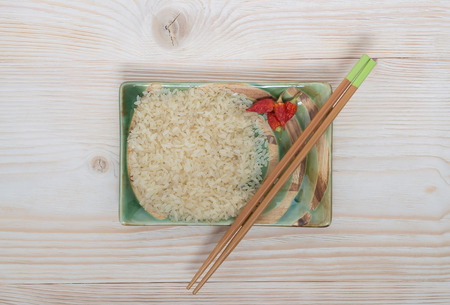not ready: Rice with chopsticks in a bowl on the table in its raw form Stock Photo