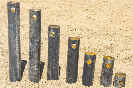 tubular: rusty pipes stand in a row on the growth on the ground