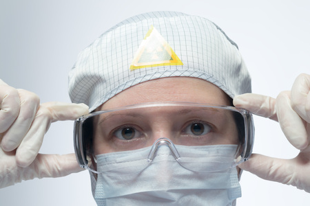protective eyewear: Scientist putting on protective eyewear Stock Photo