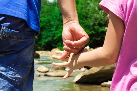 manos unidas: Padre e hija se han unido en la orilla del r�o Foto de archivo