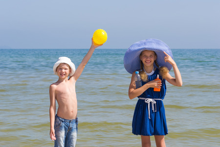 necessary: Girl and boy show that it is necessary to take from the sun on the sea