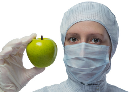 bioengineering: girl in a suit laboratory shows green apple