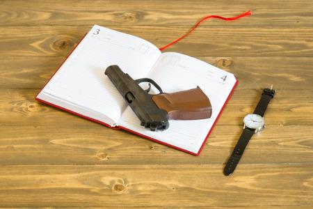 gun lying on the diary next to the clock
