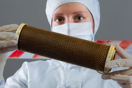 nuclear waste disposal: in the hands of the scientist filter cleaning dirt Stock Photo