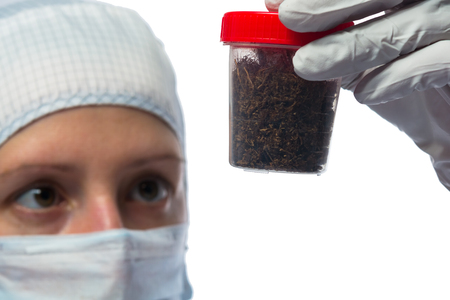 protective suit: Scientist in protective suit examines soil