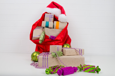 bag with gifts on the table around the decorations for the Christmas tree