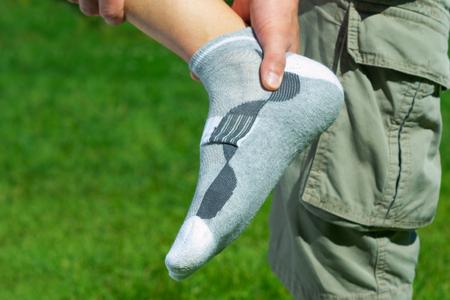 massage homme: la douleur dans le pied, les pieds sur le fond d'herbe verte