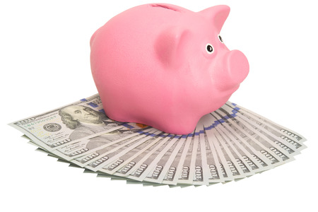 pink piggy bank standing on a large stack of money Stock Photo