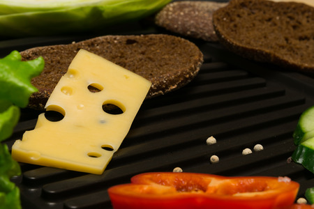 piece of cheese fell from the bread on a grill Stock Photo