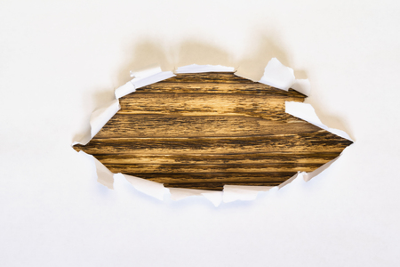 Wooden background of torn white paper