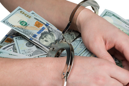 hands tied for a bribe handcuffs on dollars background Stock Photo
