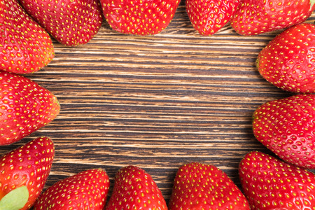 background beautiful strawberries lying around the board, in the middle of a place under an inscription