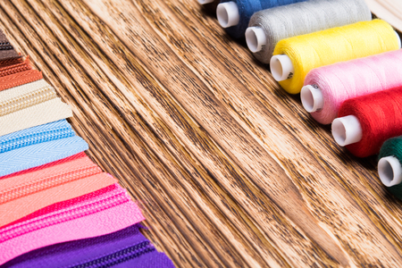 laid: colored thread laid out in front of lightning on a wooden table Stock Photo