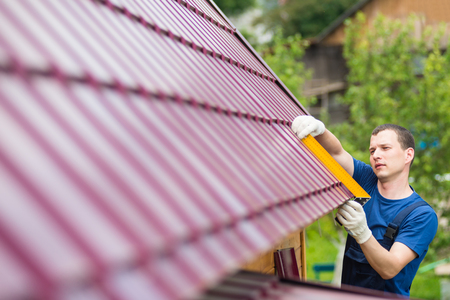 sheathing: master on repair of roofs makes measurements tool Stock Photo