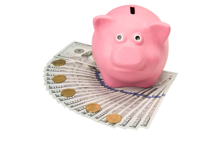 Pink piggy bank stands on dollars on a white background Stock Photo