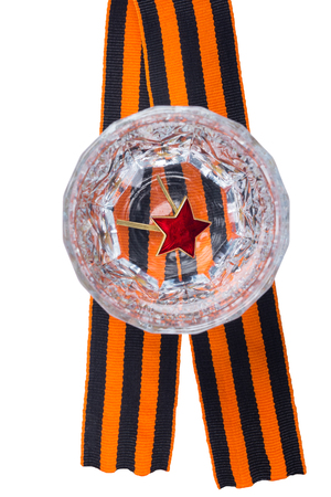 Red star on the bottom of a faceted glass in Russian vodka, to the day of victory, stands on the St. George ribbon