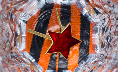 Red star in a faceted glass of vodka for the day of victory