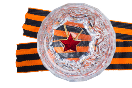 Red star on the bottom of a faceted glass in Russian vodka, to the day of victory, stands on a St. George ribbon, on an isolated white background