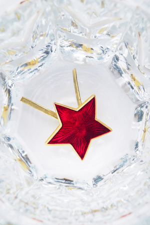 Red star lies in a glass with vodka, close-up concept Stock Photo