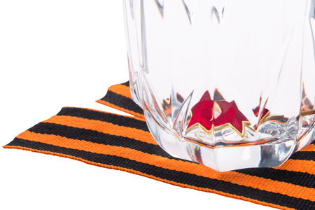 Red star lies in a glass, standing on an orange ribbon, on a white background