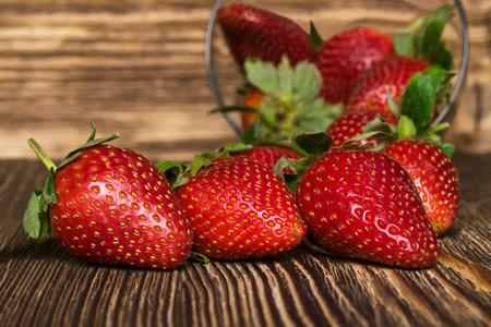 three beautiful strawberries lying on dark board, amid bowls Stock Photo