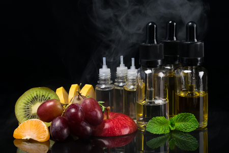 Fruit and flavors in bottles for an electronic cigarette, concept on a black background with a steam