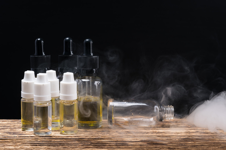 Oil in bottles for perfume and electronic cigarettes, on a dark background