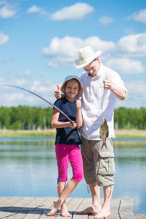 girl and a dad on vacation caught a fish on a fishing tackle at the river