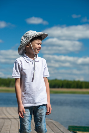 boy in hat on the background of the lake looking to the side