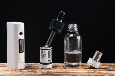 vaping set and liquid with  on a dark background Stock Photo
