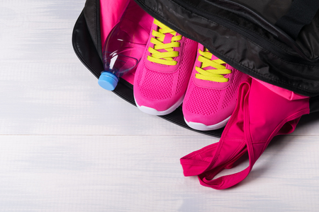 earbud: Sports things pink color for sports in a bag on a light background Stock Photo