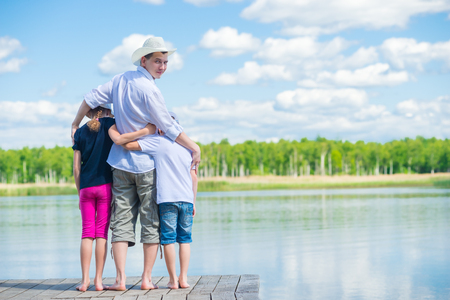 Children came to the river with their father in a hat, beautiful nature Stock Photo