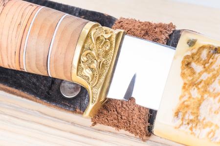 schönes Blattmesser vom Halfter auf dem Hintergrund des Holztischs Standard-Bild