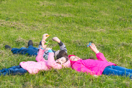 Two girls and a boy lie on the grass and play spinner Stock Photo