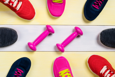shoe strings: Scattered sports shoes on a multi-colored floor, in the middle lies a set of sports dumbbells