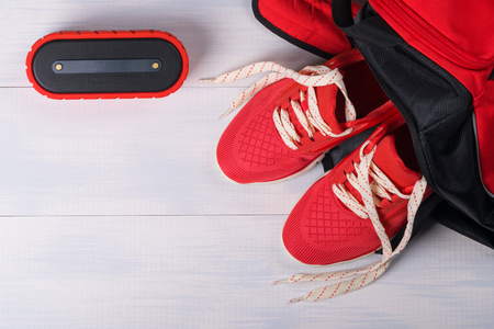 haversack: Set of things for doing sports on a wooden board and bluetooth column for music as background Stock Photo