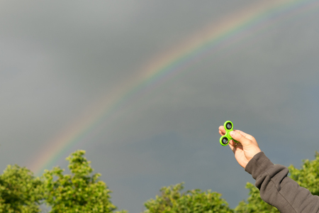 cool gadget: Hand holds a spinner against the rainbow on a gray sky Stock Photo