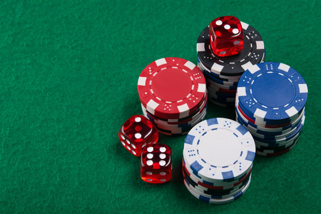 lear: dices and poker chips from above on green poker table Stock Photo