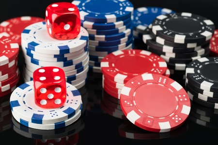 lear: Dice and poker chips on top of black poker table Stock Photo
