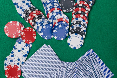 cards and poker chips with red dices on a green poker table