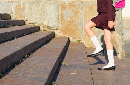 Fille en uniforme scolaire avec un sac à dos marchant sur les marches Banque d'images - 83287395